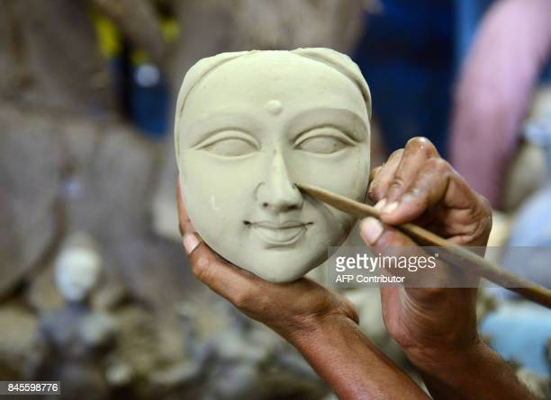 An Indian artist works on a statue of the Hindu goddess Durga ahead of the forthcoming DushheraVijaya Dashami festival at a workshop in Hyderabad on...