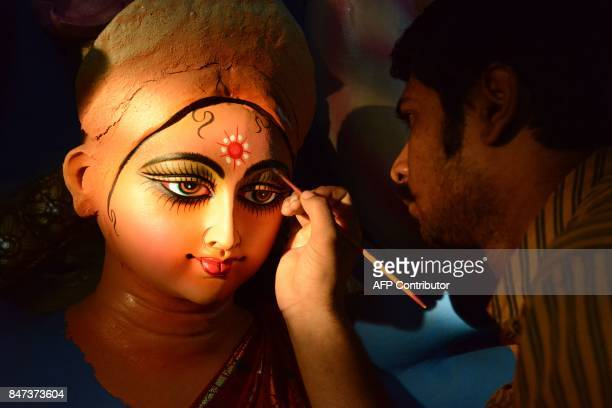 An Indian artist works on a statue of the Hindu goddess Durga ahead of the forthcoming 'DushheraVijaya Dashami' festival at a workshop in Hyderabad...
