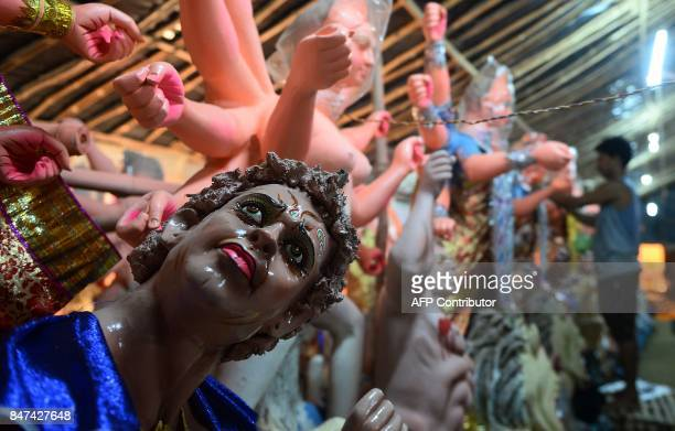 TOPSHOT An Indian artist works on a statue of the Hindu goddess Durga ahead of the forthcoming Navratri Durga festival at a workshop in Allahabad on...