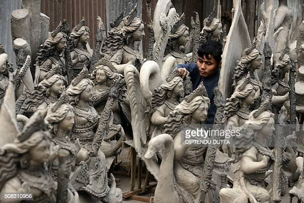 An Indian artist works on an idol of the Hindu goddess Saraswati at the artisans village known locally as Kumartoli in Siliguri on February 4 2016...