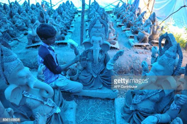 An Indian artist works on ecofriendly figures of Hindu deity Ganesha at a blue tarpcovered workshop on the outskirts of Hyderabad on August 21 2017...