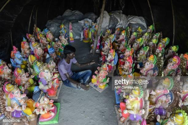 An Indian artist works on idols of the elephantheaded Hindu deity Ganesha at a small workshop ahead of the Ganesh Chaturthi festival in Jalandhar on...