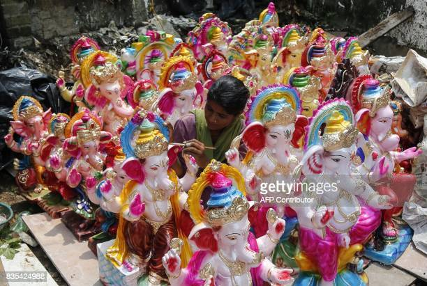 An Indian artist works on idols of the elephantheaded Hindu deity Ganesha at a roadside stall ahead of the Ganesh Chaturthi festival in Jammu on...