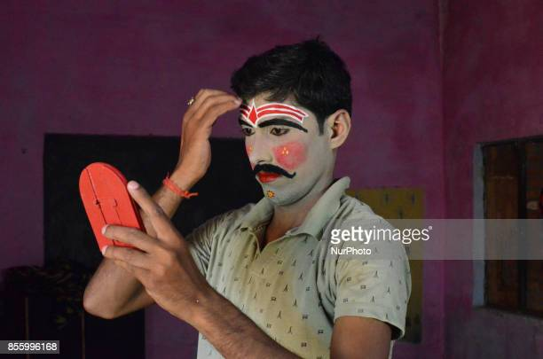 An Indian artistdressed as a character prepares himself brfore traditional Ramleelaa play narrating the life of Hindu God Ramon ocassion of Dussehra...