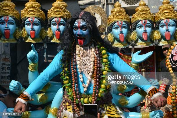 An Indian artists dressed as the Hindu deity Mata Kali performs a dance during a religious procession on the occasion of 'Maha Shivaratri' festival...