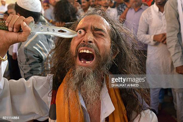 An Indian ascetic Muslim puts a sharp object into his eye as a demonstration of faith at the shrine of Sufi saint Khwaja Moinuddin Chishti during the...