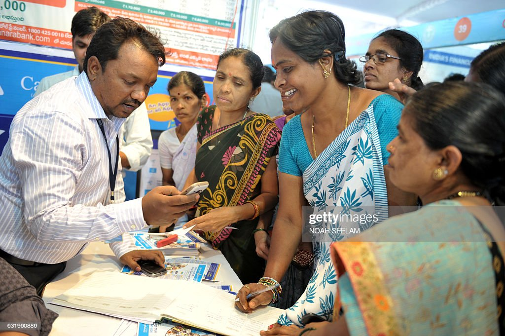An Indian bank employee (L) explains to visitors about account transactions from a mobile phone with a Aadhaar or Unique Identification (UID) card during a Digi Dhan Mela, held to promote digital payment, in Hyderabad on January 18, 2017. The Digi Dhan mela is a government initiative aimed at digital transformation in the country following the recent demonetization. / AFP / Noah SEELAM