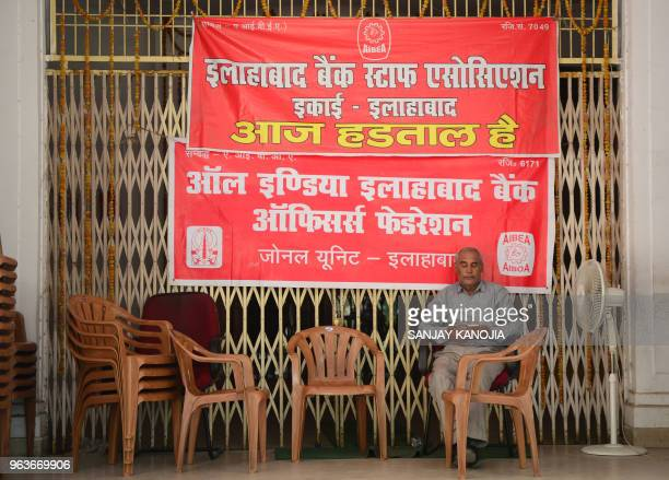 An Indian bank employee sits outside a closed branch during a twoday nationwide strike in Allahabad on May 30 2018 Nearly one million Indian public...