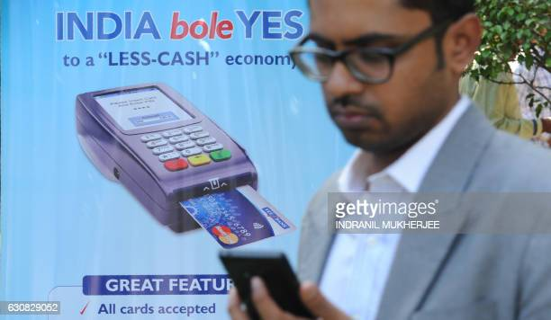 An Indian bank teller checks his phone as he walks past a poster advertising electronic payments at a Digital Wealth Fair in Mumbai on January 3 2017...