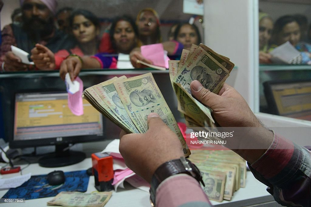 An Indian bank teller counts out notes as people gather inside a bank to deposit and exchange 500 and 1000 rupee notes in Amritsar on November 15...