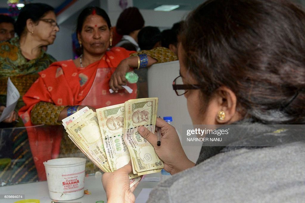 An Indian bank teller counts out notes as people gather inside a bank to deposit 500 and 1000 rupee notes at a bank in Amritsar on November 25 2016...
