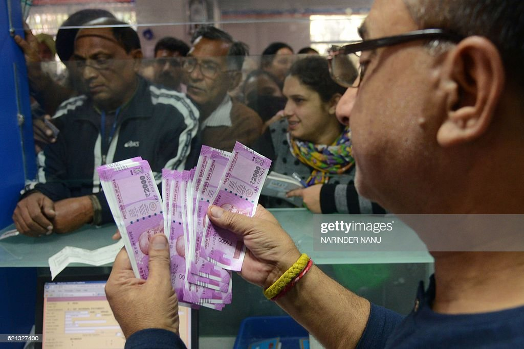 An Indian bank teller counts out notes as senior citizens wait to withdraw money at a bank in Amritsar on November 19 2016 India`s government asked...