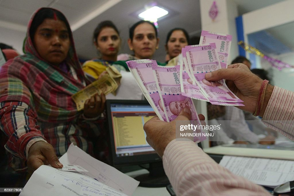An Indian bank teller hands over notes as people gather inside a bank to deposit and exchange 500 and 1000 rupee notes in Amritsar on November 15...