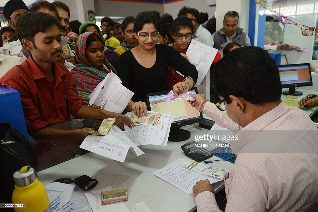An Indian bank teller works as people crowd inside a bank to deposit and exchange 500 and 1000 rupee notes in Amritsar on November 15 2016 Long...