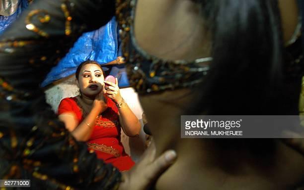 An Indian bar dancer adjusts her dress as another dancer applies makeup prior to a performance at a suburban bar cum restaurant in Bombay 06 May 2005...