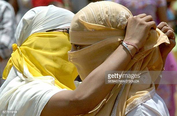 An Indian bar girl ties a scarf around her colleagues face as they seek to hide their identities before taking part in a demonstration in Bombay 03...