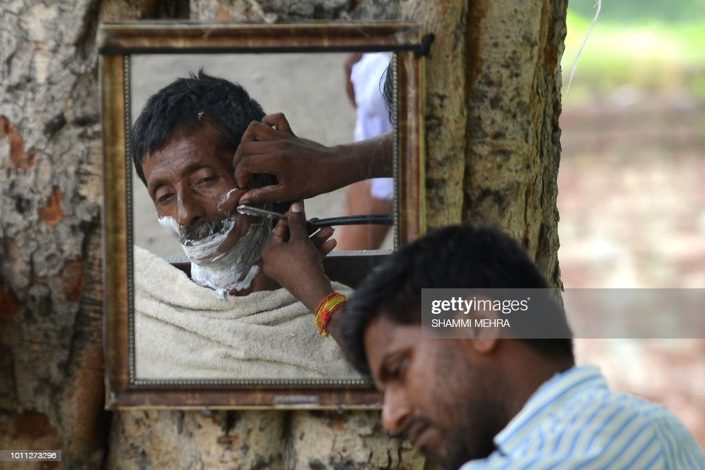 An Indian barber shaves a customer at a road side stall in Jalandhar on August 5 2018