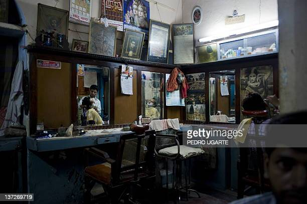 An Indian barber works in his shop in Varanasi on July 22 2009 Varanasi is believed to be about 3000 years old making it one of the oldest...