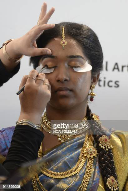 An Indian beautician applies eye liner during a demonstration at the Beauty Trade Expo in Hyderabad on February 5 2018 In total 55 cosmetics and...