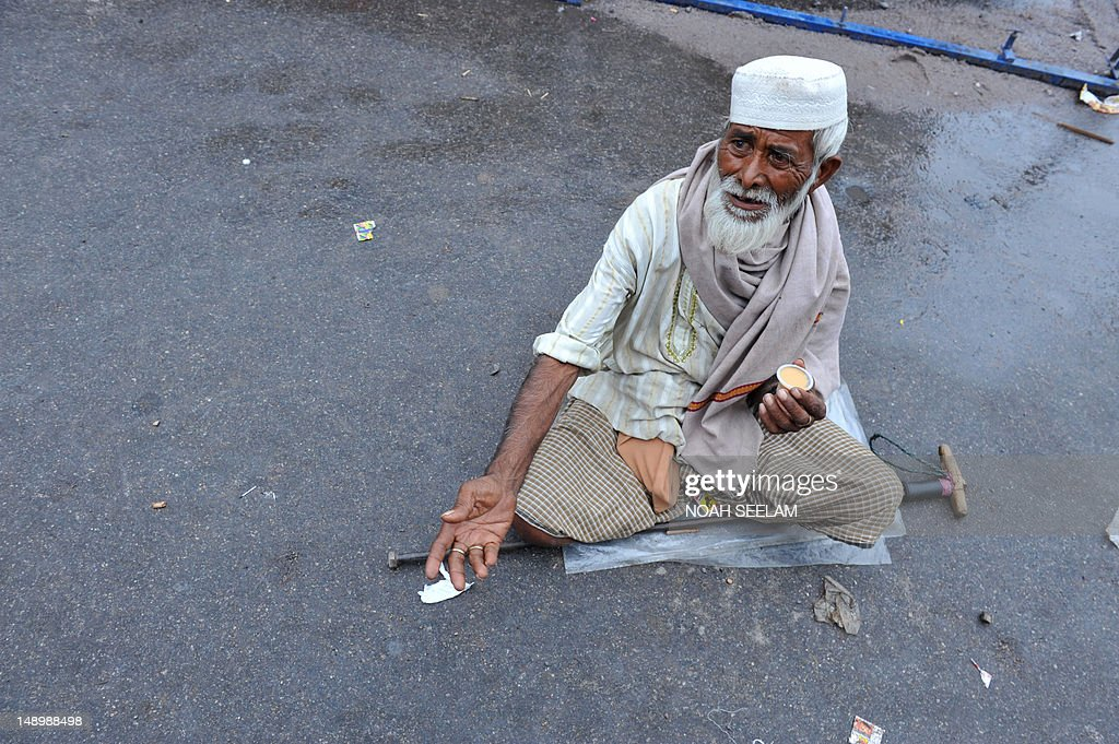 An Indian beggar reaches out for alms on : News Photo