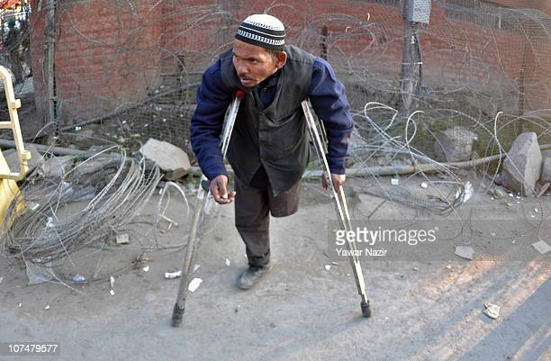An Indian beggar with crutches begs on a road on December 9 2010 in Srinagar the summer capital of Indian administered Kashmir India Kashmir has...