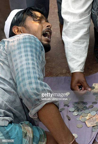 An Indian begger begs for alms outside the Jama Masjid on the last Friday of the holy month of Ramadan in New Delhi 28 October 2005 Indian Muslims...