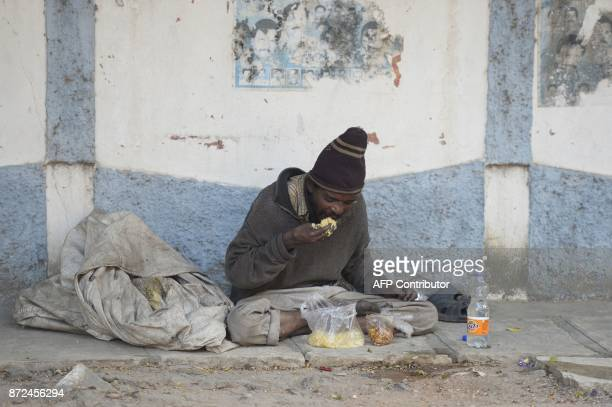 An Indian begger eats food on the side of the road in Hyderabad on November 10 2017 A city in southern India has banned begging in public places...