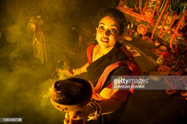 An Indian Bengali Hindu devotee performs Dhunuchi Nach dance in front of an idol of the goddess Durga during Arti ritual in New Delhi on October 18...