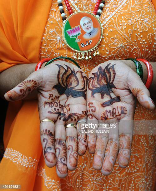 An Indian Bharatiya Janata Party supporter displays her palms adorned with henna art of the BJP party symbol outside the party headquarters in New...