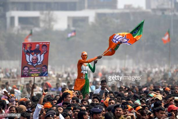 TOPSHOT An Indian Bharatiya Janata Party supporter waves a flag among the crowd of other supporters listening to Prime Minister Narendra Modi during...