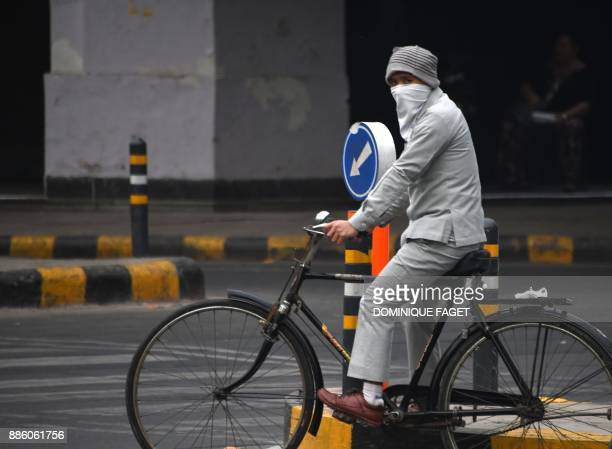 An Indian biker wearing face protection against air pollution rides on the road amid heavy smog in New Delhi on December 5 2017 The United Nations on...