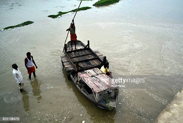 An indian boatman sails his boat along with goodsto the dry placein flooded water of River Gangesin Allahabad on July2015