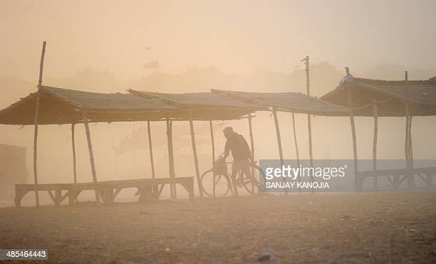 An Indian boatman wheels his bicycle through a dust storm after taking a holy dip at the Sangam the confluence of the rivers Ganges Yamuna and...