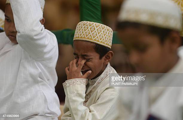 An Indian Bohra Muslim boy cries as he listens to a speech by the community's new spiritual leader Syedna Mufaddal Saifuddin at a mosque in Mumbai on...