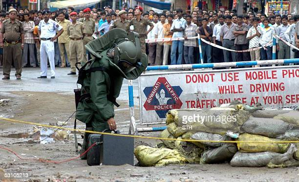 An Indian bomb disposal expert is watched by a large crowd as he reaches towards an unclaimed briefcase in the Maligoan District of Guwahati 20 June...