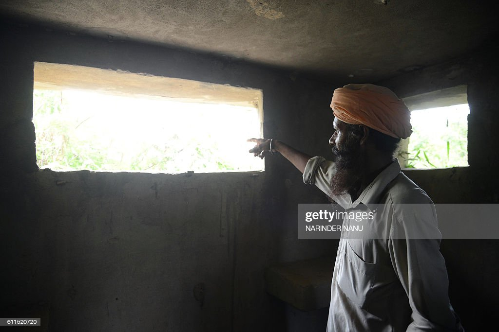 An Indian border area villager looks out of a military bunker at the Indian/Pakistan border village Chak Allah Bakash about 45km from Amritsar on...