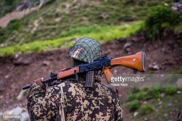 An Indian Border Security Force soldier guards a highway as Indian army convoy makes way towards Leh, bordering China, on June 19, 2020 in Gagangir,...
