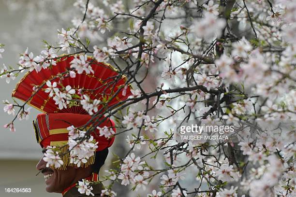 An Indian Border Security Force soldier is pictured behind a blossoming almond tree during a ceremony for a fallen comrade killed in yesterday's...