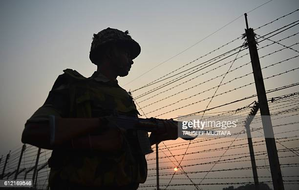 TOPSHOT An Indian Border Security Force soldier patrols along a fence at the IndiaPakistan border in RS Pora southwest of Jammu on October 3 2016 /...