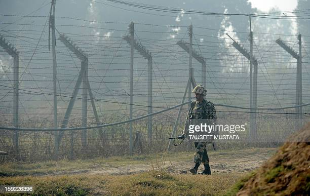 An Indian Border Security Force soldier patrols along the border fence at an outpost along the IndiaPakistan border in SuchitGarh 36 kms southwest of...