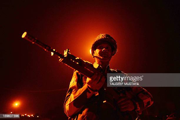 An Indian Border Security Force soldier patrols along the border fence at an outpost along the IndiaPakistan border in Abdulian 38 kms southwest of...