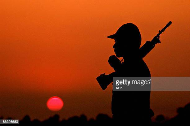 An Indian Border Security Force soldier stands guard as the sun sets over Narayanpur close to Agartala Airport in India's northeastern state of...