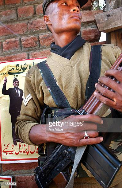 An Indian Border Security Force soldier stands next to election campaign posters for Jammu and Kashmir state chief minister Farooq Abdullah that were...