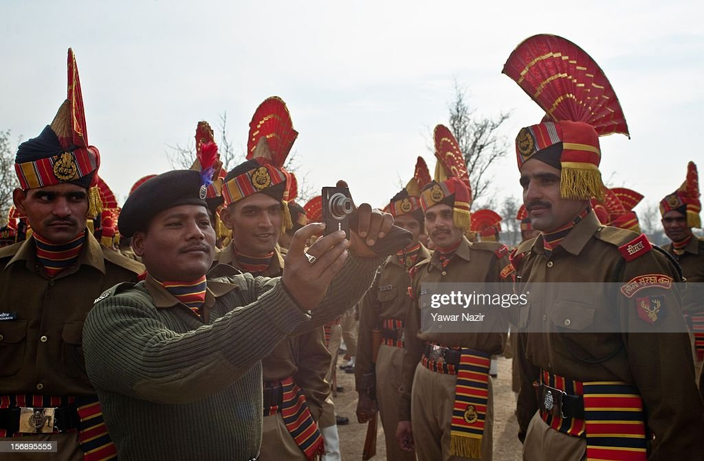 An Indian Border Security Force (BSF) soldier takes photographs of his colleagues before their passing out parade on November 24, 2012 in Humhama, on the outskirts of Srinagar, the summer capital of Indian administered Kashmir, India. 545 new trained recruits of the Indian paramilitary Border Security Force constables took oaths during their passing out parade after successfully completing 36 weeks of basic training which involved physical fitness, weapons handling, map reading, counter-insurgency operations and human rights. The recruits will join Indian soldiers to fight militants in Kashmir, a spokesman of the paramilitary BSF said. India has already close to a million soldiers posted in Jammu and Kashmir, making the disputed Himalayan region one of the most militarized zone in the world