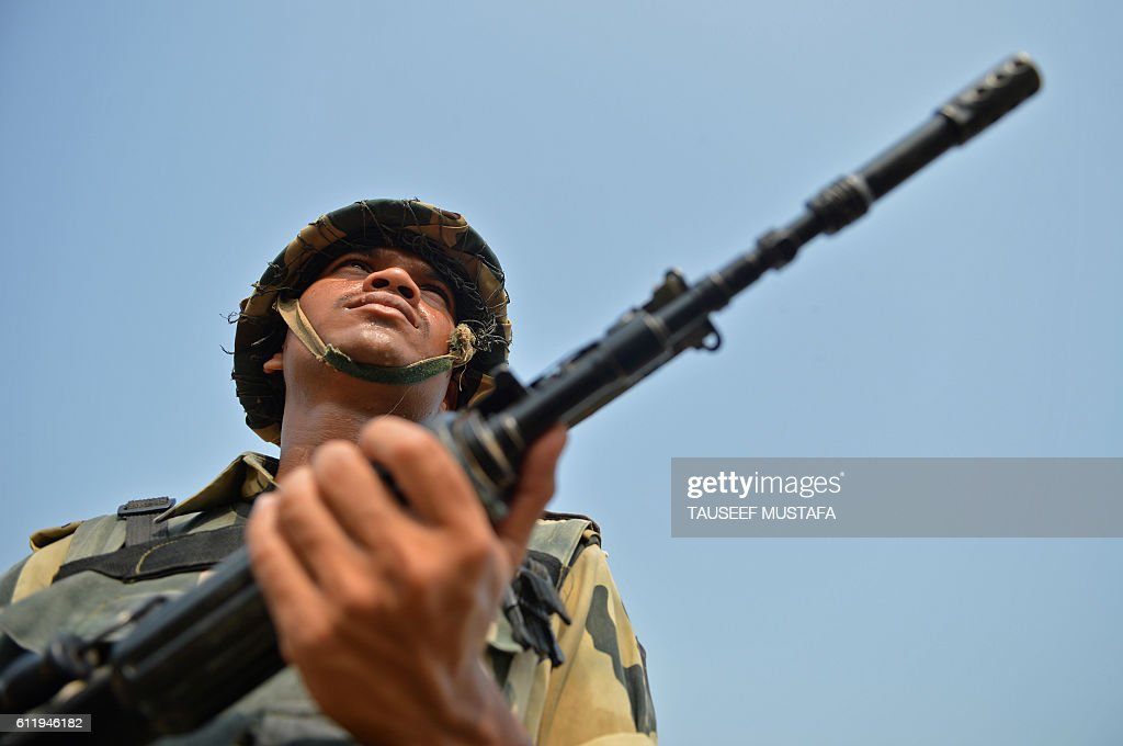 An Indian Border Security Force soldier takes up position with colleagues at an outpost along a fence at the IndiaPakistan border in RS Pora...