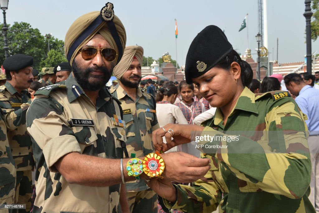 An Indian Border Security Forces member ties a `Rakhi` or sacred thread onto the wrist of Indian Border Security Forces Deputy Inspector General JS...