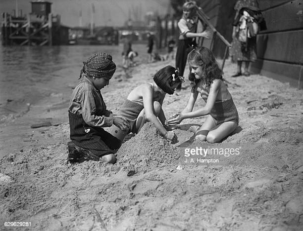 An Indian boy and two girls making a sandcastle on a beach on the Thames opposite the Tower of London 15th August 1939