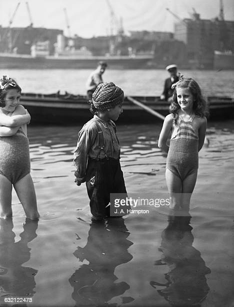 An Indian boy and two girls paddling in the Thames opposite the Tower of London 15th August 1939