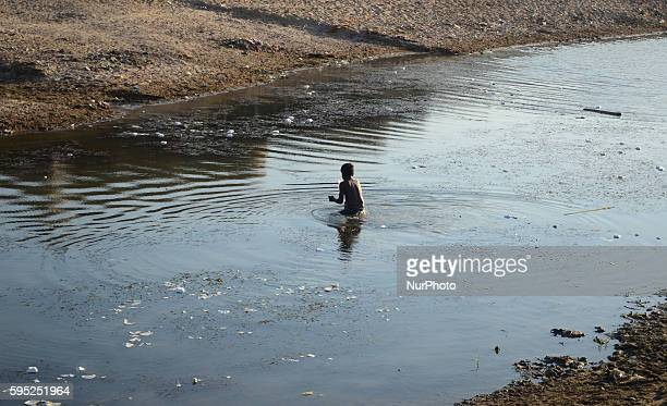 An Indian boy catches fishes on the polluted banks of River Yamuna in the outskirts of Allahabad on March 102016The Yamuna has been reduced to a...
