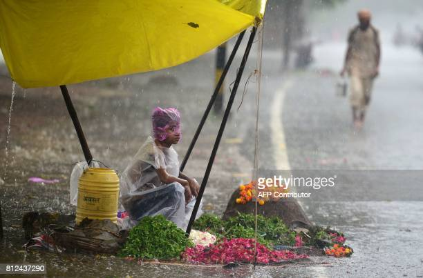 TOPSHOT An Indian boy covers himself with a plastic sheet as he waits for customers at a flower stall during heavy rain in Allahabad on July 11 2017...